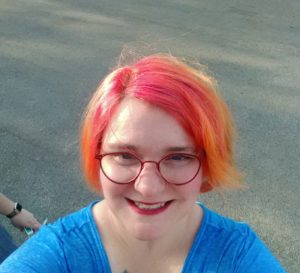 Image: Me, Katrina, with vibrant sunset-colored hair, a bright pink fading into a glorious orange and a hint of yellow. I have my red glasses on and am wearing a blue top.