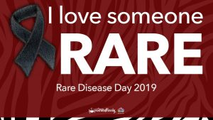 "Image: Red overlay on a black and white striped background with text that says ""I love someone rare, Rare Disease Day 2019"" and has a blue jean ribbon that represents rare genetic disorders."